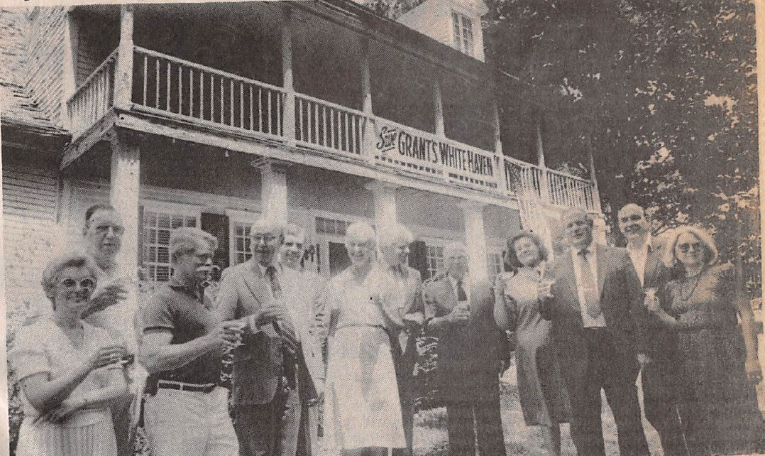 Black and white photo of a men and women toasting in front of the White Haven home.