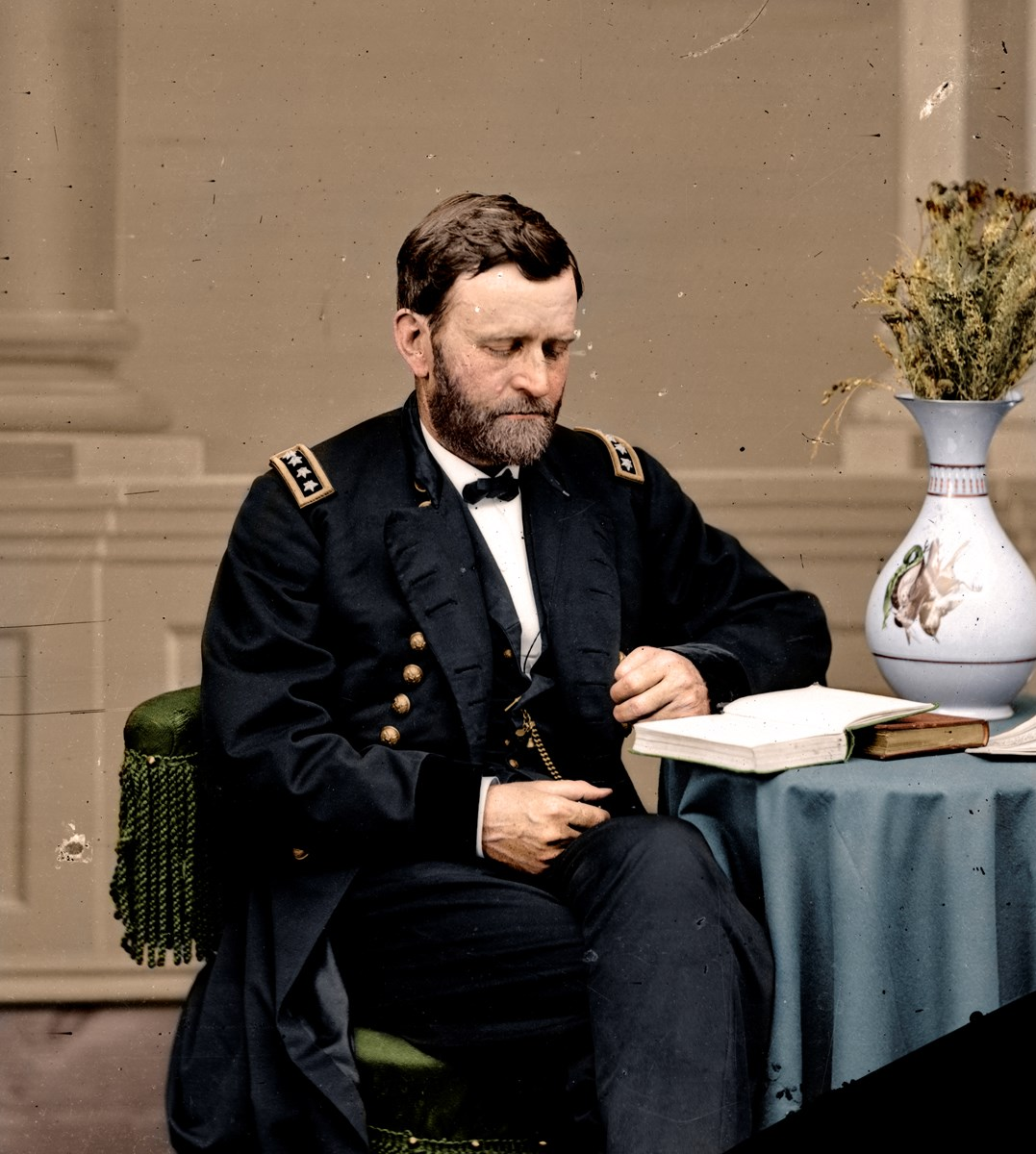 Colorized photograph Ulysses S. Grant seated and reading a book.