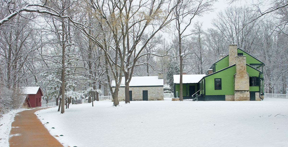 Color landscape photograph of a bright green 19th century frame house and outbuildings on a snowy day