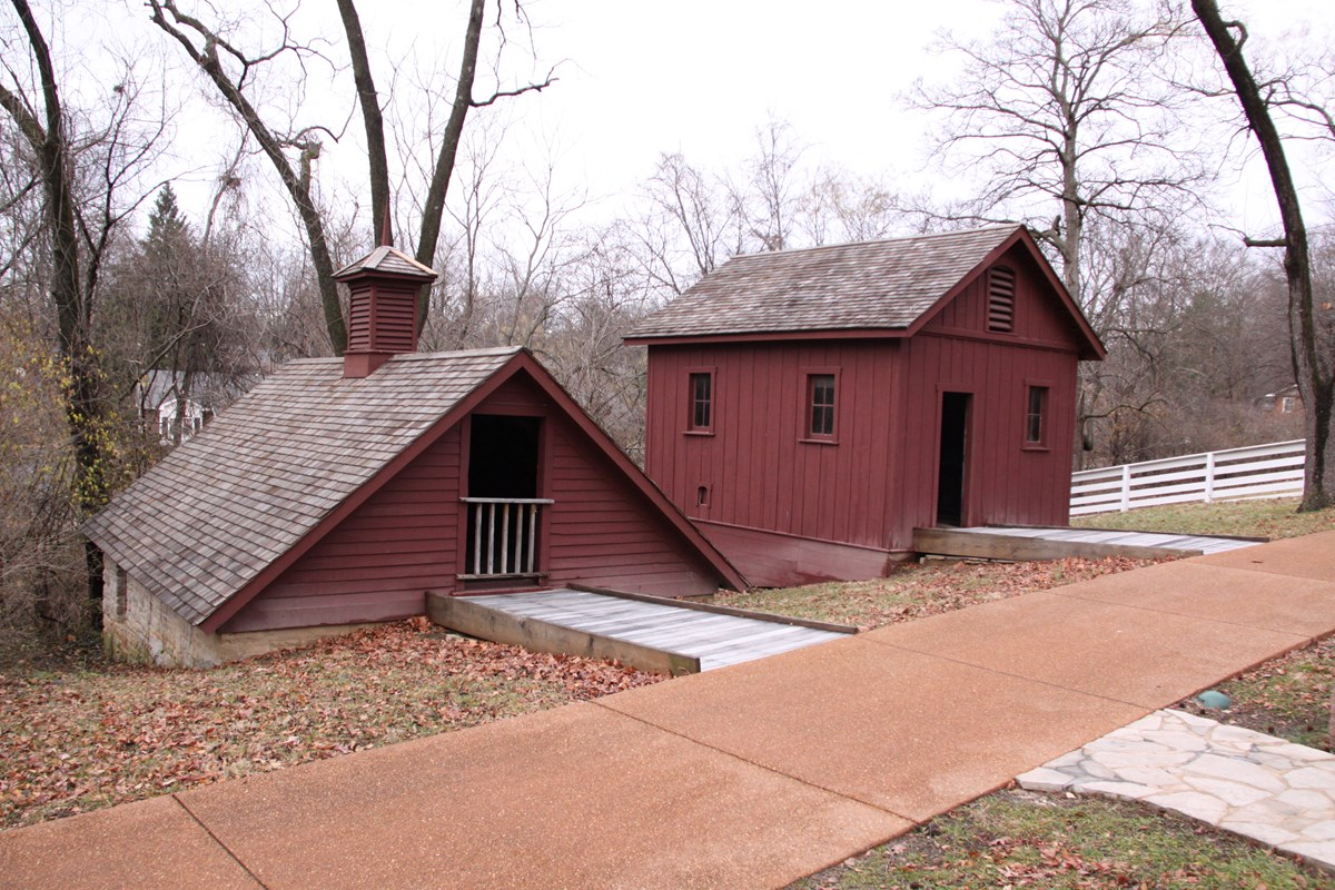Photograph of two historic outbuildings, the ice house and chicken coop.
