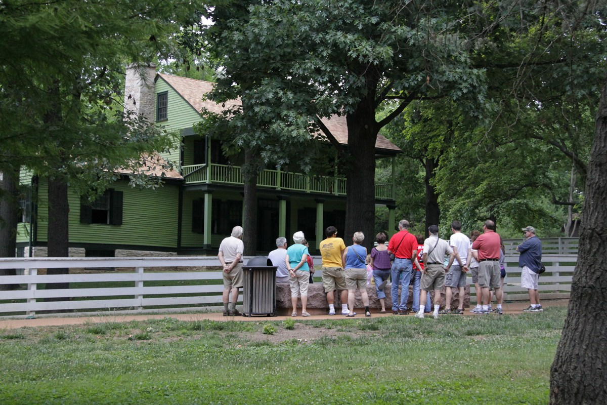 Photograph of a large group of tourists visiting the historic home on a ranger led tour.