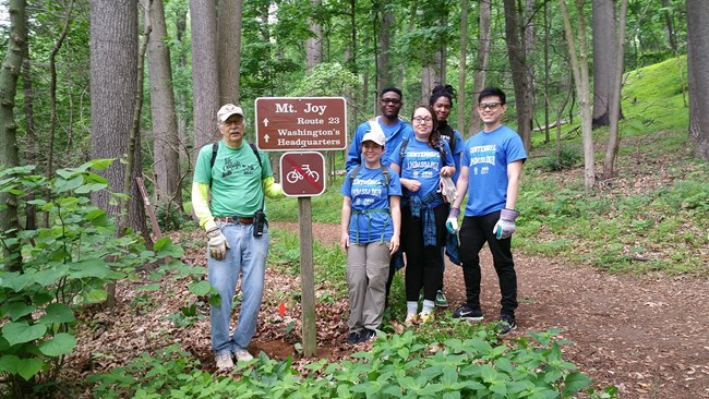 A group of young adults stand at a trailhead.