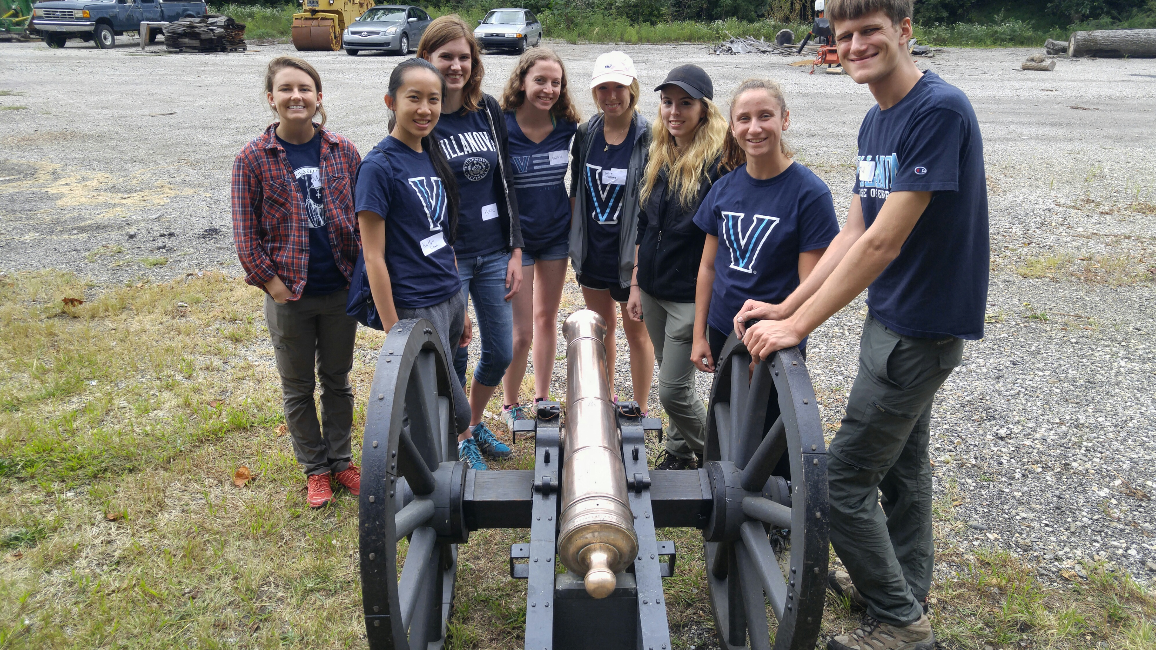 A group of college students stand around a shiny, polished cannon.