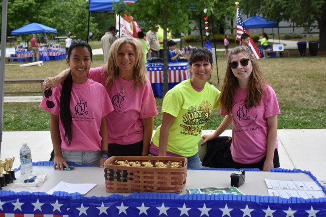 Volunteers stand behind an activity table at the July 4th Community Picnic.