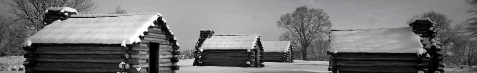Log huts are coated in a fresh layer of snow