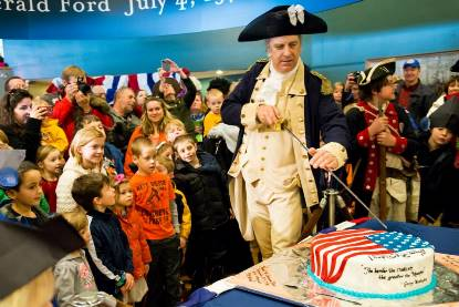 Actor portraying General Washington cuts a ceremonial birthday cake with his sword in front of a crowded room during his birthday party
