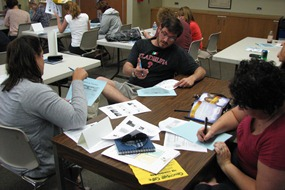 Teachers working in a group around a table with primary source documents and notes