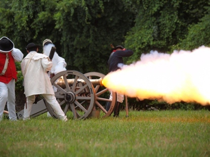 18th c reenactors brace themselves as they fire a cannon