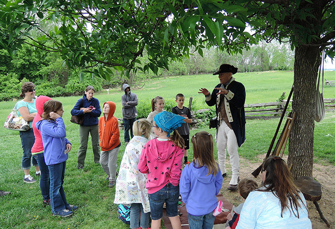 A ranger in Continental Soldier attire tells a story to children.