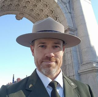 Superintendent Sims in front of granite arch monument