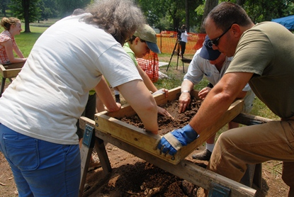 Archeology volunteers screen for artifacts