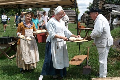 Living history volunteers take freshly baked bread out of the historic bake oven