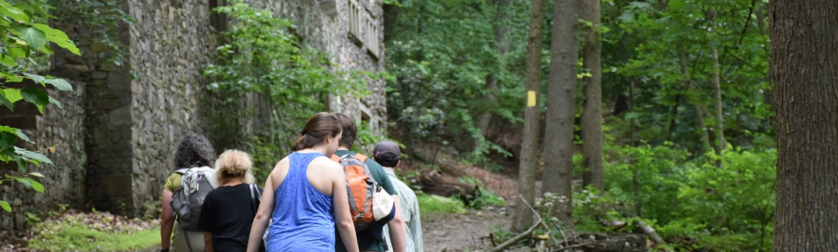 Hikers travel up hill on a wooded trail past stone ruins.