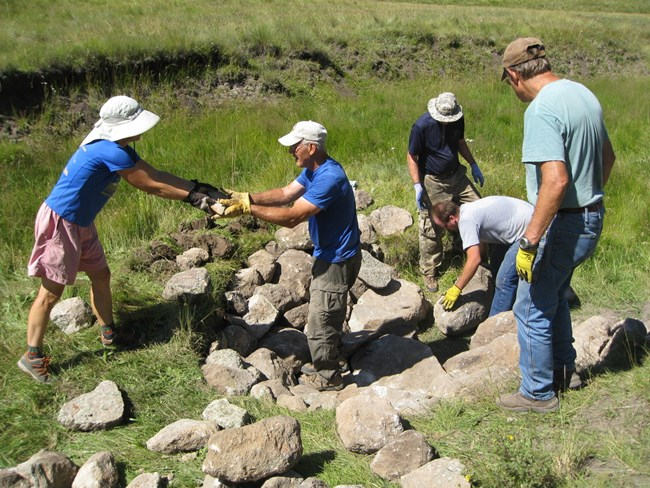 Five Los Amigos volunteers stacking rocks.