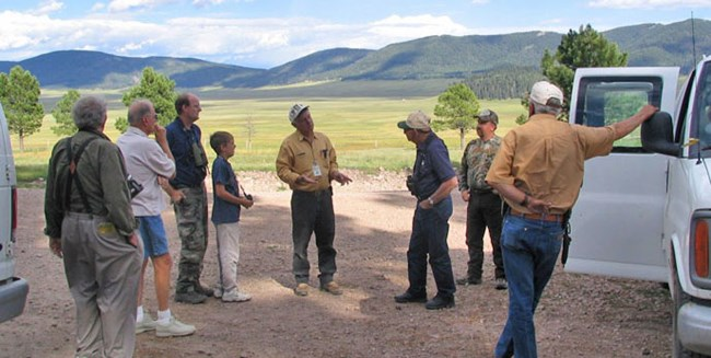 Adults and children listen to a ranger backed by scenic valley and mountains.