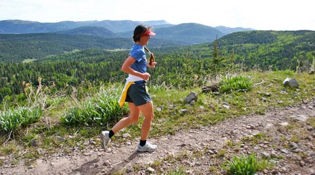 Woman running along a trail in a rugged backcountry area of Valles Caldera.