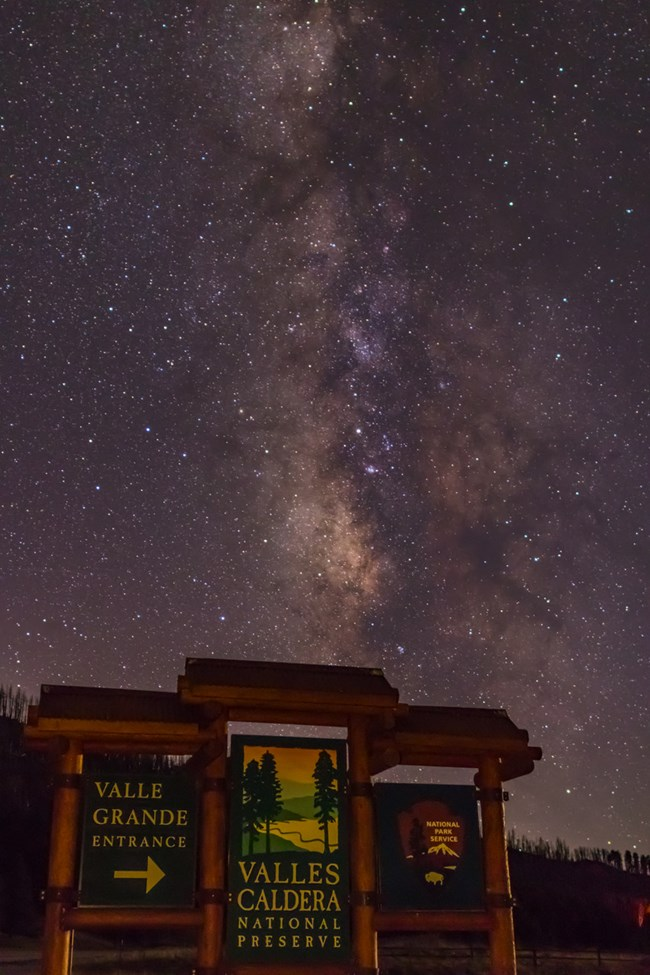 The entrance sign for Valles Caldera National Preserve under a night sky full of stars.