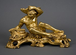 A gilt-bronze inkstand in the form of a river god. The male figure reclining on waves and holding a seashell above his head.