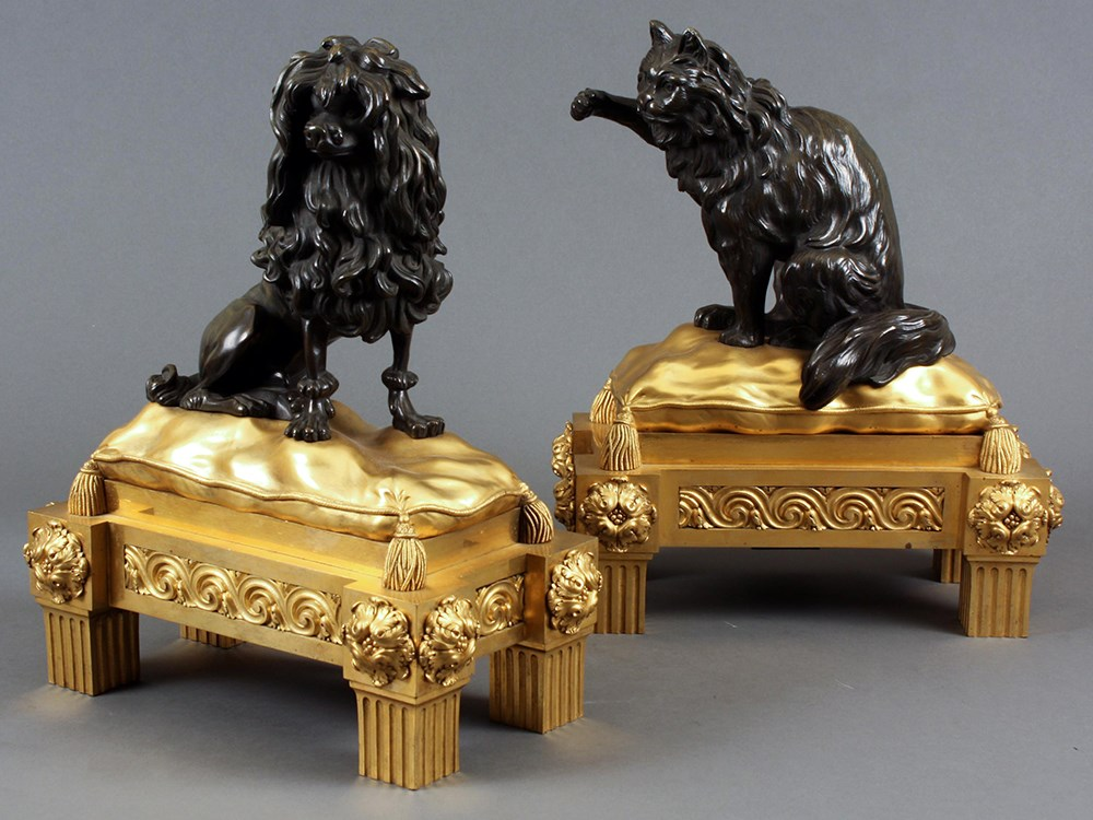 A pair of fireplace andirons, each representing a dog and a cat resting on a gilded pillow.