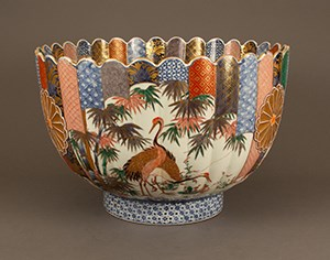 A colorful fluted, deep bowl painted with image of cranes.