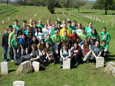University of Iowa Students pose in front of the headstones they cleaned in Vicksburg National Cemetery.