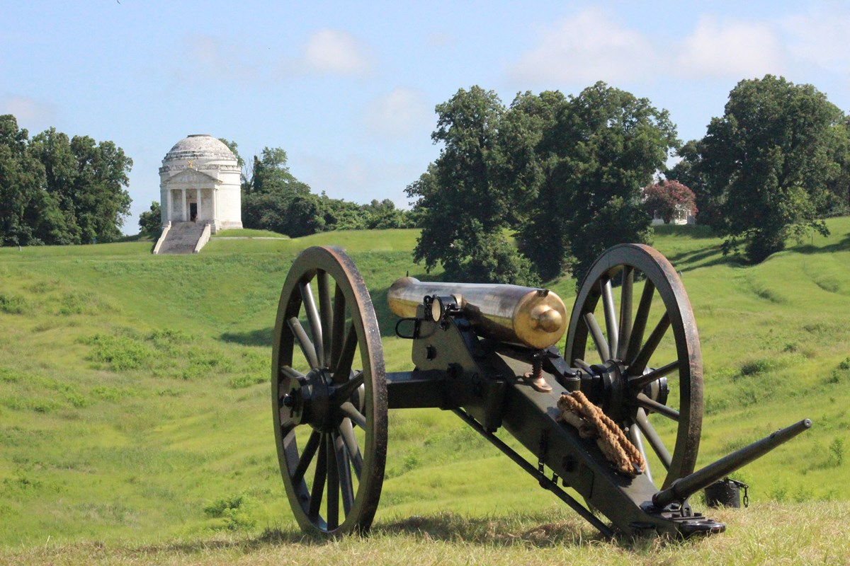 A bronze cannon facing a green field of grass and large white monument.