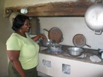 A cultural practitioner demonstrates cooking on a stove in the kitchen of a 200-year-old Danish sugar mill plantation in Virgin Islands National Park.