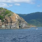 The view is shown from a boat, as it travels past a headland on the island of St. John.  Looking across the water at the cut-away portion of the headland, you can see a geologic sill.