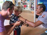 NPS Ranger pins a Junior Ranger badge on a boy while his father helps
