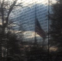 A flag at half staff reflected in the Vietnam Wall