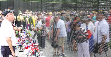 A man looks at the Vietnam Veterans Memorial on Memorial Day 2013. The wall has a large collection of flags, flowers, and memorabilia at its base, and many people's images are reflected in the wall.