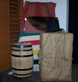 Items from the Voyageurs time period--barrel, pack, beaver pelt, beaver felt hat, blanket, and clothing.