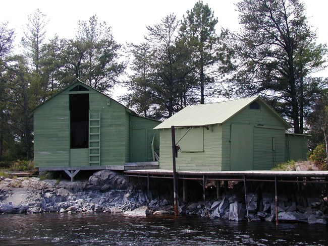 Two historic structure in park, one has a large opening that was used to put ice blocks in, the other is a small cabin like structure that was used for fish cleaning. Dock located in front of structures.