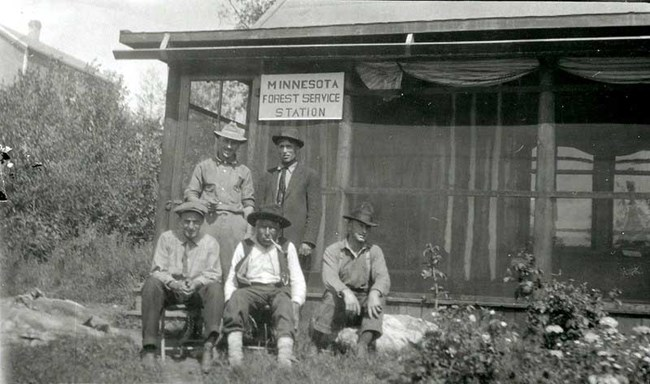 Historic photo of five men sitting in front of a screened in porch of a Minnesota Forest Service Station