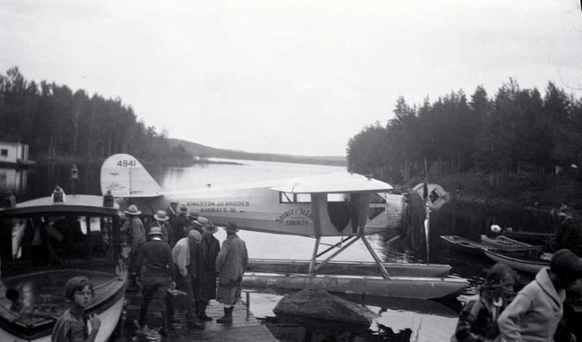 Historic photo, float plane at a dock with several people loading or unloading goods in the foreground, open water and trees in back landscape