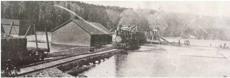 A historic photo of a railroad trestle and hoist built across the water to transport logs.