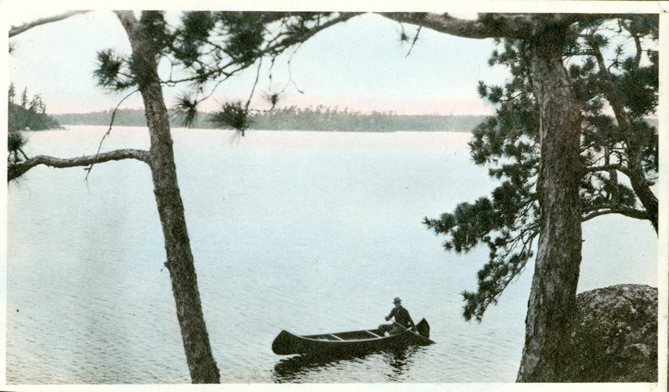Historical photo of a person canoeing on a lake