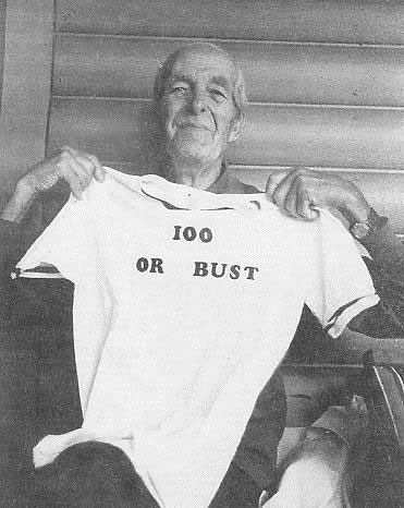 I.W. Stevens holding up a tshirt that says 100 or bust, celebrating his 100th birthday