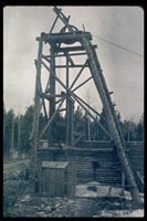 Historic photo showing a mine shaft made from timbers.