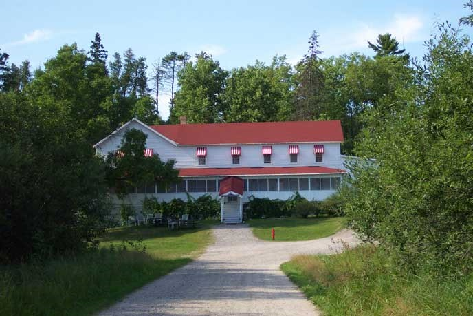 A two-story building, white siding, red roof and awnings, with large screened in porch along the front.  Surrounded by trees with a road leading up to the front and center of the building.