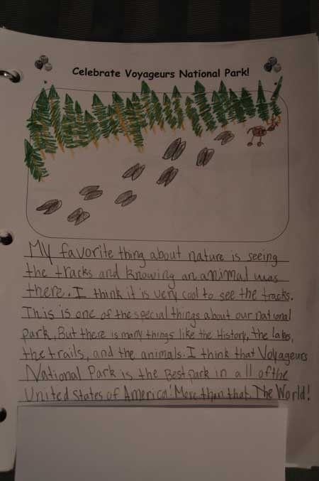 A students artwork depicting pine trees with hoof tracks across the page and a antlered animal at the end of the tracks