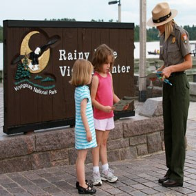 Two girls are sworn in as Junior Rangers by a Park Ranger.