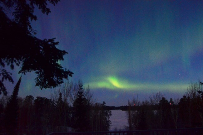 Several faint green curtains of light glow against dark skies above a frozen lake shore.
