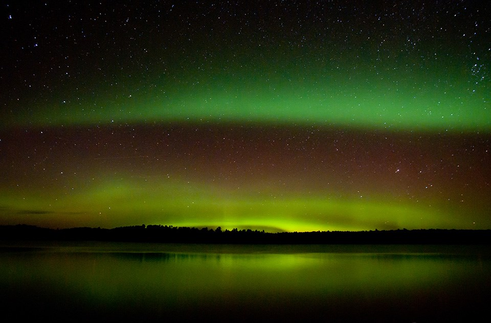 Two bright green curtains of light shine against a dark, starry sky over a tree-lined horizon and a scenic lake.
