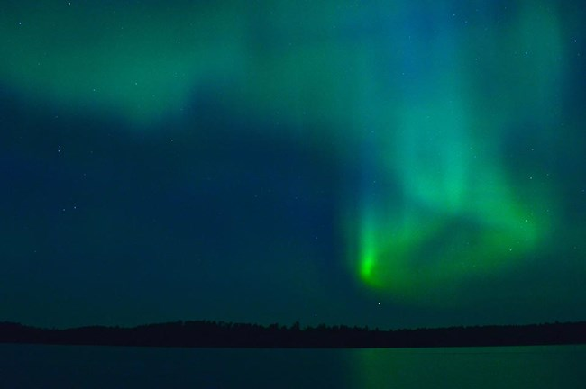 Bands of green and blue light appear to dance and swirl in the dark night sky above a scenic lake.