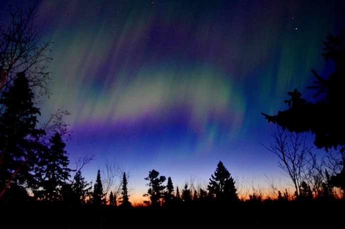 Green, Red, and Yellow Northern Lights over a dark horizon.