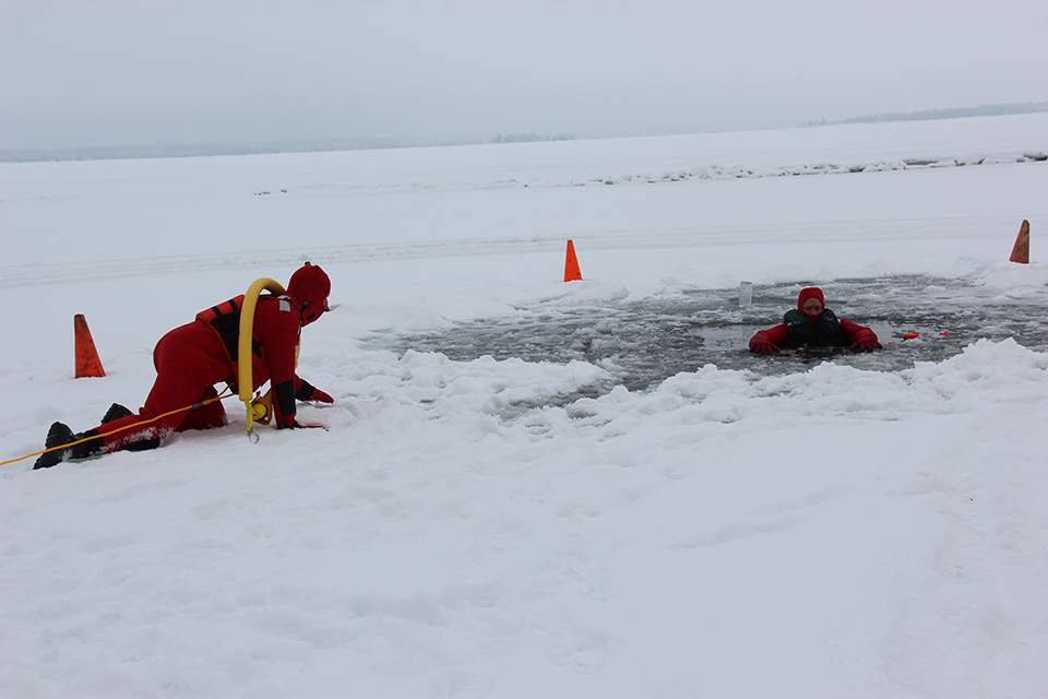 A person in a float suit and life jacket crawls out on the frozen lake surface toward another person submerged in a ice hole as part of a ice rescue training.