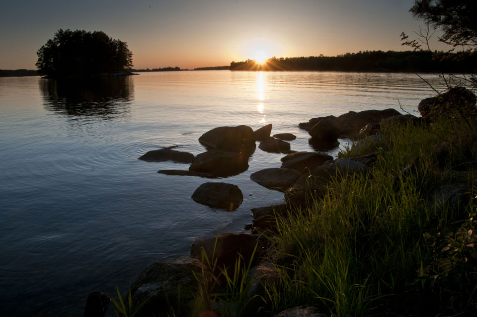 Sun is setting over a tree line, with a reflection in the water. Island located in background with a rocky shoreline in the foreground.