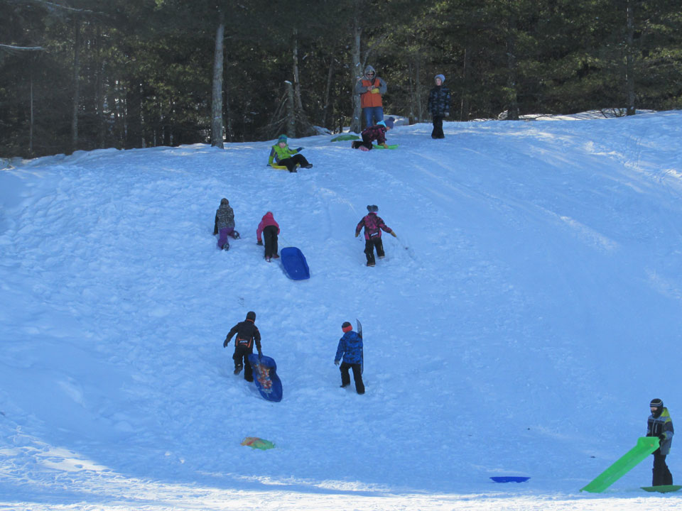 Many youth climbing up a snowhill, others getting ready to slide down.