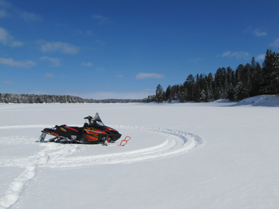 Snowmobile sitting on the frozen lake surface